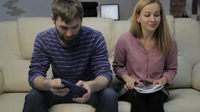 O estudante louro lê suas notas, e seu noivo que senta-se no sofá e nos smartphones dos usos video estoque