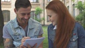 O estudante masculino escreve algo em seu caderno fotografia de stock royalty free