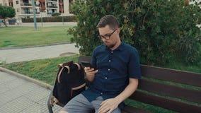 O estudante masculino está descansando em um banco em um parque, usando o smartphone moderno filme
