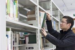 O estudante novo encontra livros na biblioteca Imagem de Stock