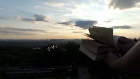 O estudante novo está e olha através de um livro no por do sol no slo-mo filme