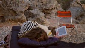 O estudante novo Girl Lying no colchão inflável no acampamento e lê o EBook em uma praia HD video estoque