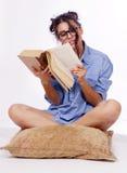 O estudante novo lê um livro foto de stock