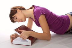 O estudante novo olha no livro fotos de stock royalty free