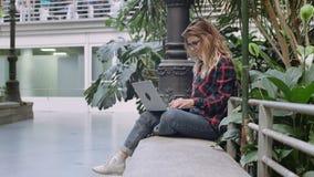 O estudante ou a mulher de negócio nova trabalham no portátil filme