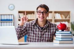 O estudante que quebra o piggybank para pagar por propinas Fotografia de Stock