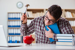 O estudante que quebra o piggybank para pagar por propinas Fotografia de Stock Royalty Free