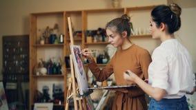O estudante talentoso da escola de arte está pintando a imagem com seu professor que trabalha junto no estúdio completamente das  vídeos de arquivo