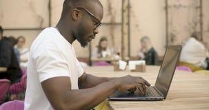 O estudante trabalha no portátil video estoque