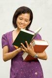 O estudante universitário asiático leu a literatura fotos de stock