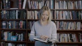 O estudo adolescente bonito da menina e aprende A estudante loura esperta leu uma literatura, girou páginas e olhou a câmera sens filme