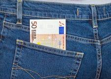 O euro da cédula 50 que cola fora das calças de brim pocket Imagens de Stock Royalty Free