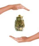 O Euro inventa em um frasco entre as mãos no fundo branco Fotografia de Stock Royalty Free
