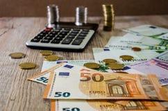 O Euro, os dólares, os centavos e a calculadora espalharam para fora em um fundo de madeira imagem de stock royalty free