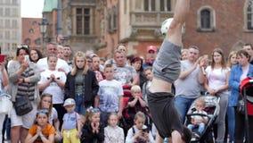 O evento da cidade, homem executa truque complicado com a bola de futebol na frente dos espectadores de admiração esfarrapados filme