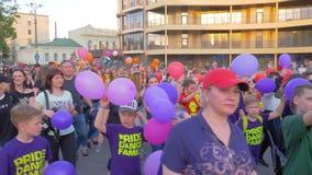 O evento da cidade, pessoa da multidão de idades diferentes com balões anda ao longo dos cantos da rua e do grito da cidade no ar vídeos de arquivo