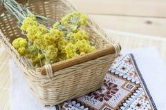 O everlast do anão floresce o ramalhete em uma cesta de vime e o guardanapo com bordado na tabela de madeira clara Foto de Stock Royalty Free