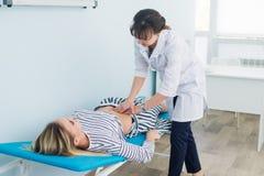 O exame abdominal, doutor está examinando o abdômen do paciente foto de stock