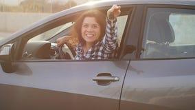 O excitador da mulher que mostra o carro fecha o sorriso feliz em seu carro novo vídeos de arquivo