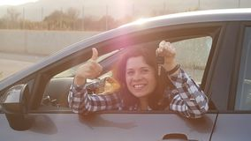 O excitador da mulher que mostra o carro fecha o sorriso feliz em seu carro novo video estoque