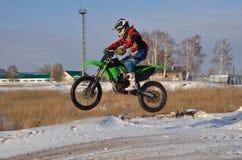 O excitador de motocicleta voa sobre o monte fora da neve imagens de stock royalty free