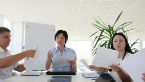 O executivo empresarial com as folhas de papel distribui atribuições para colegas no escritório branco filme