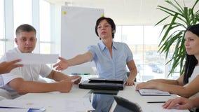 O executivo empresarial com a equipe dos sócios mantém as folhas de papel brancas na sala de reuniões moderna filme