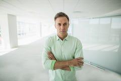 O executivo empresarial que está com braços cruzou-se no corredor do escritório Imagem de Stock Royalty Free