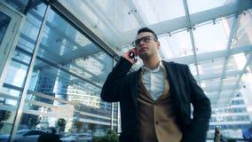 O executivo está falando no telefone ao ter uma caminhada ao lado de um prédio de escritórios filme