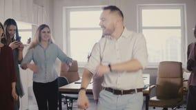 O executivo masculino caucasiano novo que faz uma dança engraçada da vitória no partido de escritório ocasional do divertimento,  filme