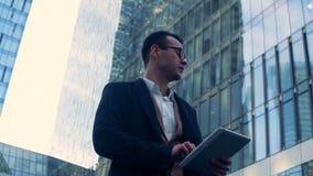 O executivo masculino está olhando em torno de um complexo do negócio, skyscrappers metragem da câmera do cinema 6K filme