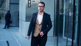 O executivo masculino está saindo de um centro de negócios Tiro épico vermelho do dragão 6K vídeos de arquivo