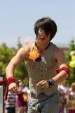 O executor de circo Twirls as bolas de fogo no festival Imagem de Stock