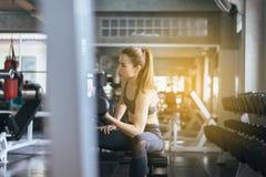 O exercício asiático desportivo da mulher com os pesos, fêmeas no sportswear faz os exercícios fotos de stock royalty free