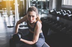 O exercício da mulher do esporte com os pesos, fêmeas no sportswear faz os exercícios no gym fotografia de stock royalty free