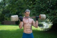 O exercício do homem com o Barbell feito da mão fora malha Imagem de Stock Royalty Free