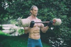 O exercício do homem com o Barbell feito da mão fora malha Imagens de Stock Royalty Free