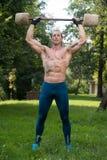 O exercício do homem com o Barbell feito da mão fora malha Fotografia de Stock Royalty Free