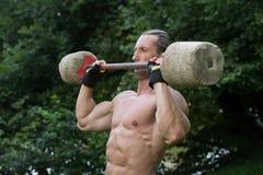 O exercício do homem com o Barbell feito da mão fora malha Fotos de Stock Royalty Free