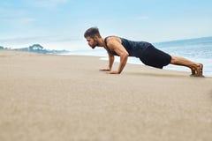 O exercício do homem da aptidão, fazendo empurra levanta o exercício na praia esportes fotografia de stock royalty free