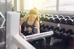 O exerc?cio f?mea bonito asi?tico forte com peso, f?mea no sportswear faz os exerc?cios no gym imagens de stock