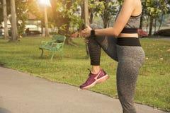 O exercício fêmea estica seu pé relaxa para muscle para correr Imagem de Stock Royalty Free