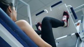O exercício na máquina da imprensa do pé, desportista levanta a plataforma pesada no gym video estoque