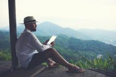 O explorador masculino novo está usando a tabuleta digital ao admirar a natureza selvagem das montanhas fotos de stock