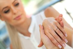 Extremo próximo acima da mão das meninas com anel de noivado. Imagens de Stock