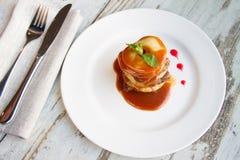 O fígado de vitela com maçãs colocou camadas com molho em uma placa branca Fotografia de Stock Royalty Free