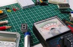 O fabricante bonde de DIY utiliza ferramentas componentes na placa de esteira verde do corte foto de stock