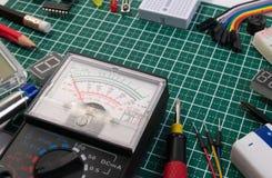 O fabricante bonde de DIY utiliza ferramentas componentes na placa de esteira verde do corte fotos de stock