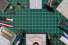 O fabricante bonde de DIY utiliza ferramentas componentes na placa de esteira verde do corte imagem de stock
