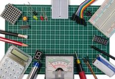 O fabricante bonde de DIY utiliza ferramentas componentes na placa de esteira verde do corte fotos de stock royalty free